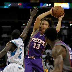 Nov 19, 2009; New Orleans, LA, USA; Phoenix Suns guard Steve Nash (13) passes the ball to forward Amare Stoudemire (1) as New Orleans Hornets guard Darren Collison (2) defends on the play during the second half at the New Orleans Arena. The Hornets defeated the Suns 110-103. Mandatory Credit: Derick E. Hingle-US PRESSWIRE