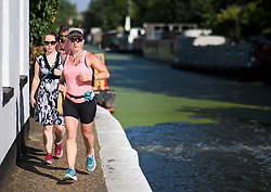 © Licensed to London News Pictures. 24/07/2018. London, UK. Commuters and a jogger make their way along the canal towpath at Little Venice in central London, as warm temperatures in the capital continue. Forecasters are predicting record temperatures later this week. Photo credit: Ben Cawthra/LNP