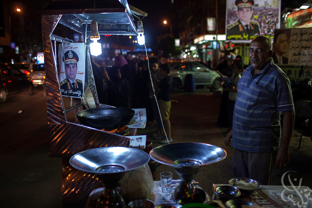 """An Egyptian falafel vendor decorates his cart  in the Dokki Square area of Giza with a photo of  Gen. Abdel Fattah El Sissi, the head of Egypt's military, during mass demonstrations called for across Egypt by El Sissi, Egypt on Friday July 26, 2013. EL Sissi had asked Egyptians to take to the streets on Friday to show the world that he had a mandate to deal with """"violence and terrorism""""."""