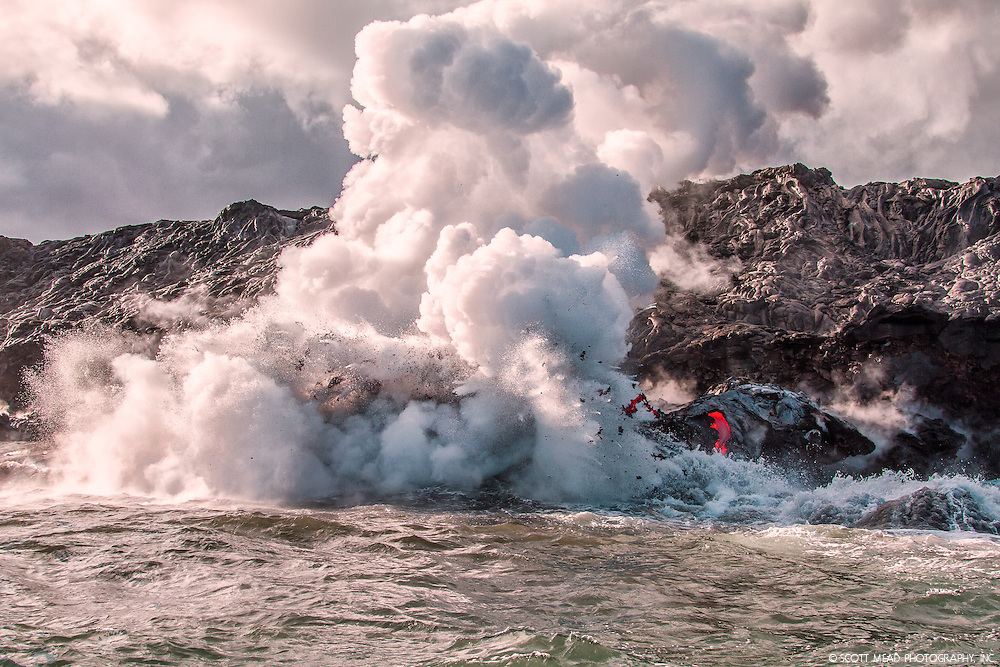 Flowing lava into ocean, creating steam cloud, and producing flying chunks of lava, Kilauea Volcano, Big Island, Hawaii
