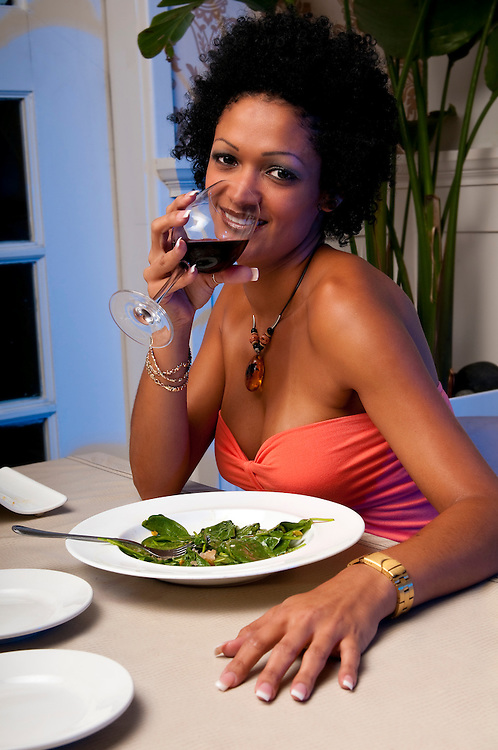 Latin woman drinking wine in a restaurant very sexy.