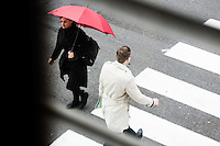 Brussels Belgium 2 June 2016.A woman in Black with a red umbrella and a man in  a creme raincoat crossing the street close to the European Comission
