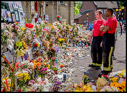 June 22, 2017 - London,  United Kingdom - London firefighters pause to look and read messages on the flowers for dead at Grenfell Town in West London, the tower  caught fire on June 14th, where Seventy-nine people are believed to have died after a huge fire engulfed the tower block. Theresa May announced today that there could be six hundred  high-rise buildings that have cladding similar to Grenfell Tower as Theresa May reveals panels on three blocks have already been assessed as 'combustible'  (Credit Image: © Andrew Parsons/i-Images via ZUMA Press)