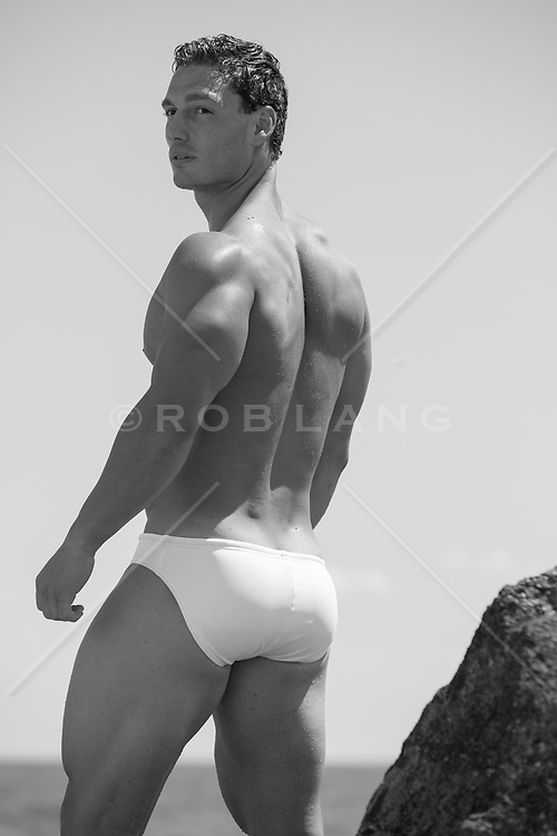sexy muscular man in a speedo by the ocean