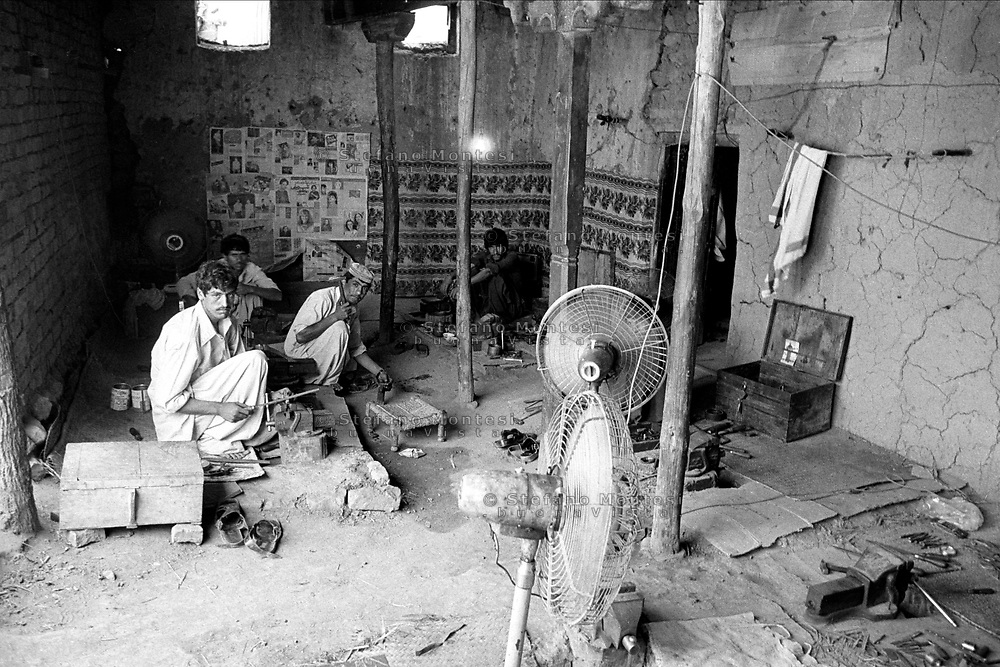 Pakistan 1986 .Darra Adamkhel is Pakistan's largest weapons bazaar and factory, renowned for its gun making expertise since the late 19th century, Darra is a sprawl of hundreds of workshops where some 3,500 gunsmiths toil on replica weapons..workshop for the construction of pieces of weapons