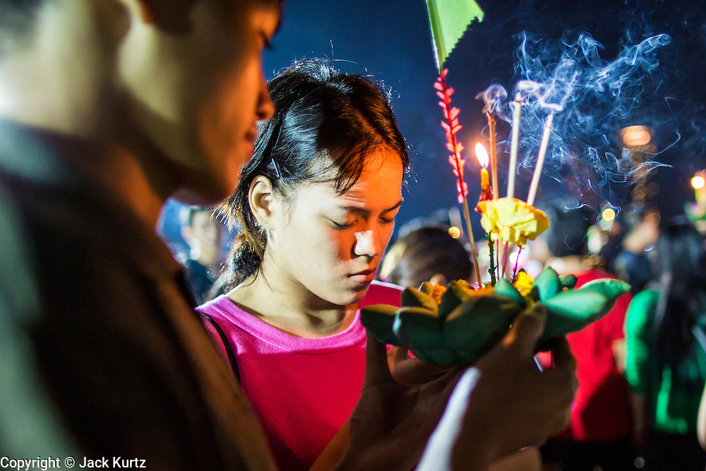 28 NOVEMBER 2012 - BANGKOK, THAILAND:  A couple prays before floating their krathongs on Loy Krathong at Wat Yannawa in Bangkok. Loy Krathong takes place on the evening of the full moon of the 12th month in the traditional Thai lunar calendar. In the western calendar this usually falls in November. Loy means 'to float', while krathong refers to the usually lotus-shaped container which floats on the water. Traditional krathongs are made of the layers of the trunk of a banana tree or a spider lily plant. Now, many people use krathongs of baked bread which disintegrate in the water and feed the fish. A krathong is decorated with elaborately folded banana leaves, incense sticks, and a candle. A small coin is sometimes included as an offering to the river spirits. On the night of the full moon, Thais launch their krathong on a river, canal or a pond, making a wish as they do so.   PHOTO BY JACK KURTZ