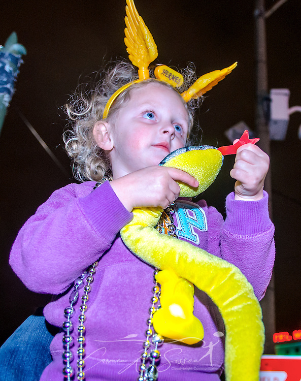 A little girl holds a stuffed snake she caught as the Krewe of Hermes Mardi Gras parade rolls down St. Charles Avenue at Lee Circle, Feb. 28, 2014, in New Orleans, Louisiana. (Photo by Carmen K. Sisson/Cloudybright)