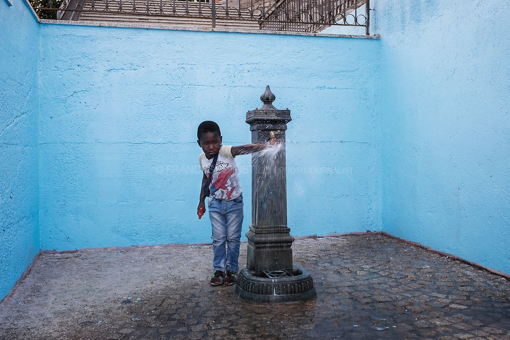 A refugee kid playing with water fountain.  RIACE (ITALY) 06/08/16