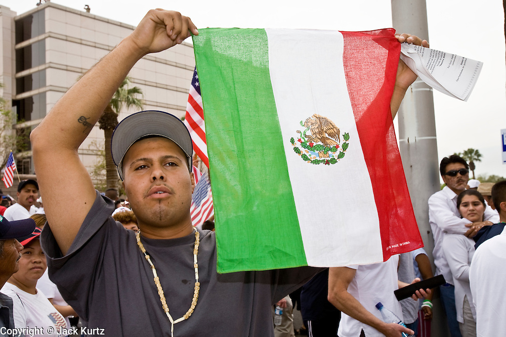 10 APRIL 2006 - PHOENIX, AZ: A Mexican immigrant waves the Mexican flag during a march for immigrants rights in Phoenix, AZ. More than 200,000 people participated in a march for immigrants's rights in Phoenix Monday. The march was a part of a national day of action on behalf of undocumented immigrants. There were more than 100 such demonstrations across the US Monday. Protestors were encouraged to wear white, to symbolize peace, and wave American flags, to demonstrate their patriotism to the US.  Photo by Jack Kurtz