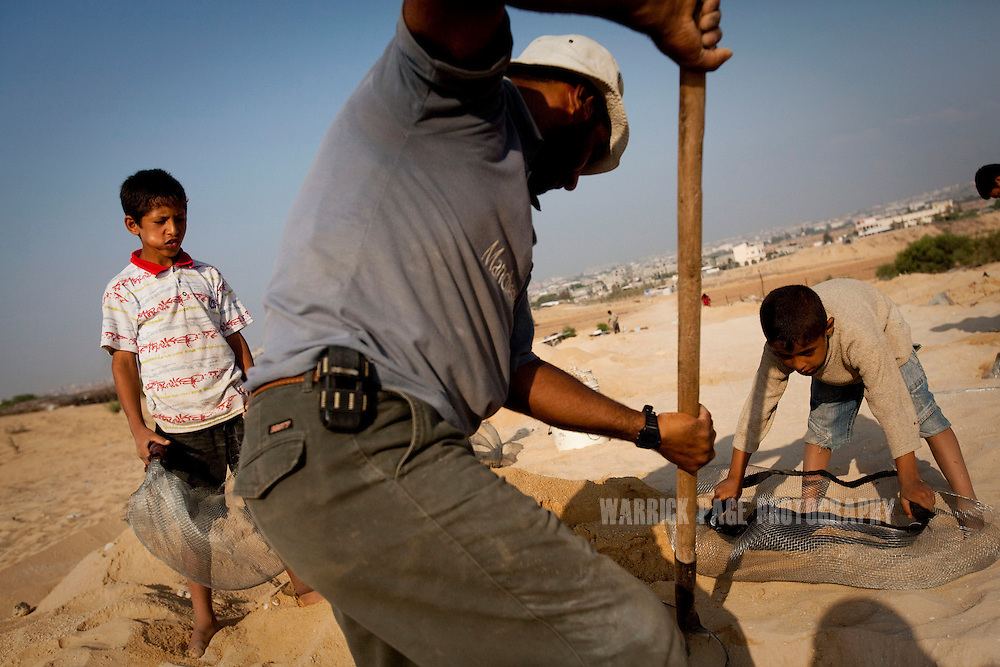 BEIT LAHIYA, GAZA STRIP - JULY 8: Saleh al-Da'ma, 38 (C), and his sons, Ali, 11 (L), and Adel 7 (R), dig for gravel from a former Israeli settlement on the Gaza/Israel border, to be sold for use in construction, on July 8, 2010, in Beit Lahiya , Gaza Strip. With Gaza's economy devastated by years of sanctions and decades of conflict, many families send their children to work. Although Israel eased its blockade in mid-June - allowing in consumer goods - little has changed for Gaza's poorer families. Unemployment runs at 40% and the majority of the population is dependent upon aid handouts for their basic needs.  (Photo by Warrick Page)