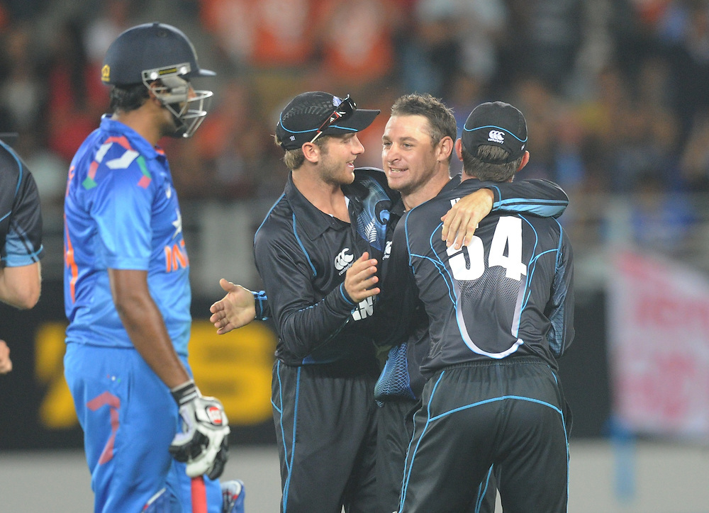New Zealand's Nathan McCullum, centre is surrounded by team  mates after dismissing India's Ravi Ashwin for 65 in the third one day International cricket match, Eden Park, Auckland, New Zealand, Wednesday, January 25, 2014. Credit:SNPA / Ross Setford