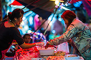 17 JANUARY 2013 - SAMUT SONGKHRAM, SAMUT SONGKHRAM, THAILAND: A vendor helps a customer in the market in Samut Songkhram. Four trains each day make the round trip from Baan Laem, near Samut Sakhon, to Samut Songkhram, the train chugs through market eight times a day (coming and going). Each time market vendors pick up their merchandise and clear the track for the train, only to set up again when the train passes. The market on the train tracks has become a tourist attraction in this part of Thailand and many tourists stop to see the train on their way to or from the floating market in Damnoen Saduak.    PHOTO BY JACK KURTZ