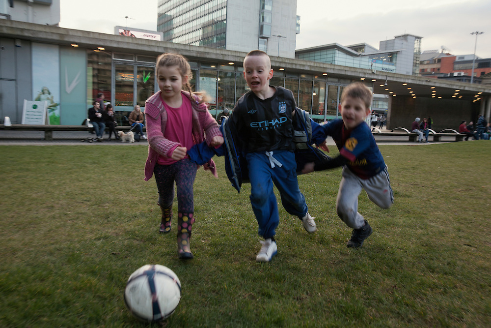 Kids playing football at Picadilly Gardens in Manchester, UK.