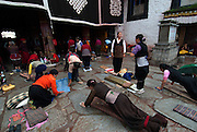 Tibetan pilgrims at the sacred Jokhang Temple (&quot;House of the Lord&quot;) in Lhasa,the holiest site in Tibetan Buddhism. It draws thousands of prostrating Tibetan pilgrims, as well as curious foreign tourists every year. <br /> <br /> The Jokhang Temple was founded in 647 by King Songtsen Gampo (r.617-49), the first ruler of a unified Tibet, and his two foreign wives who are credited with bringing Buddhism to Tibet. The king's first wife, Princess Bhrikuti,the sister of the Nepalese king, while his second wife, Princess Wencheng was the niece or daughter of the Chinese emperor.
