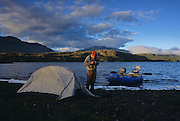 08065-Z. An angler ties on a fly at sunrise after camping on the shore of Lago Cinco in the Patagonia region of Argentina.