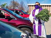 "05 APRIL 2020 - DES MOINES, IOWA:  Rev. RUSSELL LACKEY follows ""Social Distancing"" guidelines while he hands out palms during a drive through Palm Sunday service sponsored by Luther Memorial Church on the campus of Grand View University in Des Moines. About 150 people attended the service. They remained in their cars while the ministers read a short passage from the Bible, handed out palms and blessed them. On Sunday, 05 April, Iowa reported 868 confirmed cases of the Novel Coronavirus (SARS-CoV-2) and COVID-19. There have been 22 deaths attributed to COVID-19 in Iowa. Restaurants, bars, movie theaters, places that draw crowds are closed until 30 April. The Governor has not ordered ""shelter in place"" but several Mayors, including the Mayor of Des Moines, have asked residents to stay in their homes for all but essential needs. People are being encouraged to practice ""social distancing"" and many businesses are requiring or encouraging employees to telecommute.        PHOTO BY JACK KURTZ"