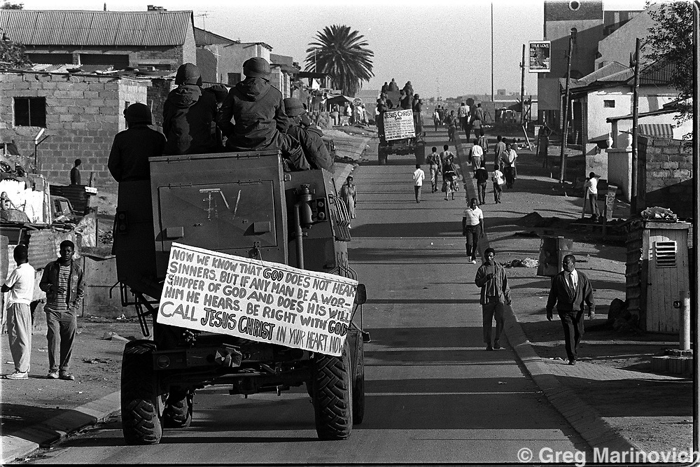 IPMG0022 South Africa, Alexander, 1992..Members of the controversial 32 army battalion patrol the streets of Alexander township in Johannesburg with placards they stole from an evangelist church. 19 Oct 1992. Thousands of people, both civilians and combatants died in the so-called Hostel War from 1989-1995..Photograph by Greg Marinovich/South Photographs