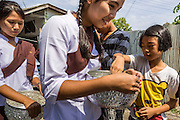 24 MAY 2013 - MAE SOT, THAILAND:  Burmese women collect donations for their temple during a procession for Visakha Puja Day in Mae Sot, Thailand. Visakha Puja (Vesak) marks three important events in the Buddha's life: his birth, his attainment of enlightenment and his death. It is celebrated on the full moon of the sixth lunar month, usually in May on the Gregorian calendar. This year it is on May 24 in Thailand and Myanmar. It is celebrated throughout the Buddhist world and is considered one of the holiest Buddhist holidays. Burmese Buddhist in Mae Sot celebrated with a procession through Mae Sot that ended with a service followed by a communal meal at Wat Pha Mai, the most important Burmese Buddhist temple in Mae Sot.   PHOTO BY JACK KURTZ