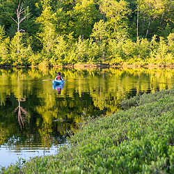 A man kayaking on Round Pond in Barrington, New Hampshire.