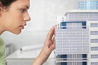 Mid adult woman inspecting architectural model profile close-up