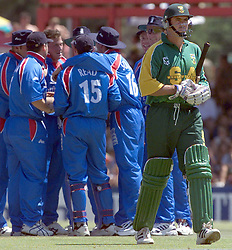 South African captain Hansie Cronje (right) departs for the pavilion after being dismissed for 2 runs, while the England team celebrate in the background, during their first one-day international at Bloemfontein, South Africa.