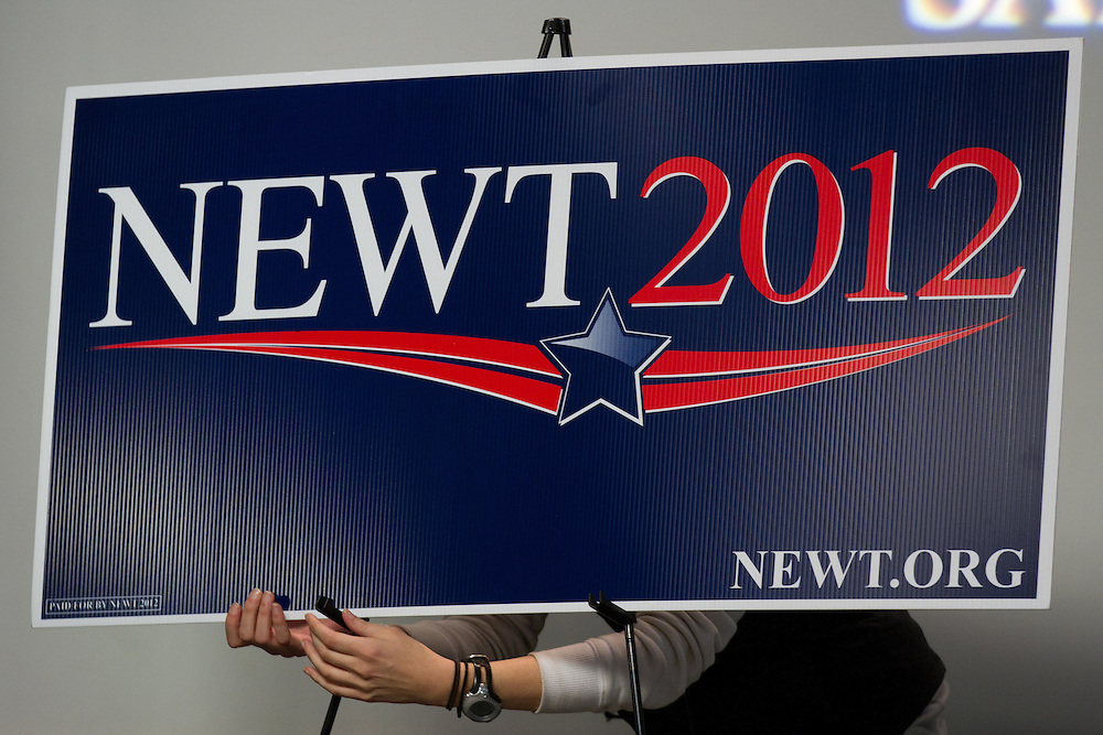 MANCHESTER, NH - JANUARY 04: A campaign worker adjusts a sign for Republican presidential candidate and former House Speaker Newt Gingrich at the New Hampshire Institute of Politics at Saint Anselm College  on January 04, 2012 in Manchester, New Hampshire. After finishing 4th in the Iowa Caucus, Gingrich continued his campaign in New Hampshire for the upcoming primary.  (Photo by Matthew Cavanaugh/Getty Images)..