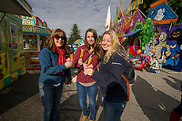 Food trucks galore lining the streets at Laconia's Pumpkin Fest on Saturday.  First stop for the Kallmerten girls (Pam, Julia and Amy) corn dogs.  (Karen Bobotas/for the Laconia Daily Sun)