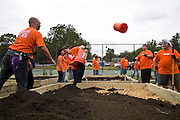 Volunteers, mostly from the Home Depot, help build a new community garden in a Richmond City park. The garden is organized by Tricycle Gardens, a Richmond organization that specializes in building and upkeeping community gardens. This new garden will provide plots for a $50 fee so that community members can produce their own food during the summer months.