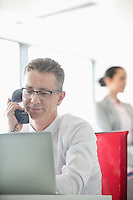 Businessman talking on telephone with colleague in background at office