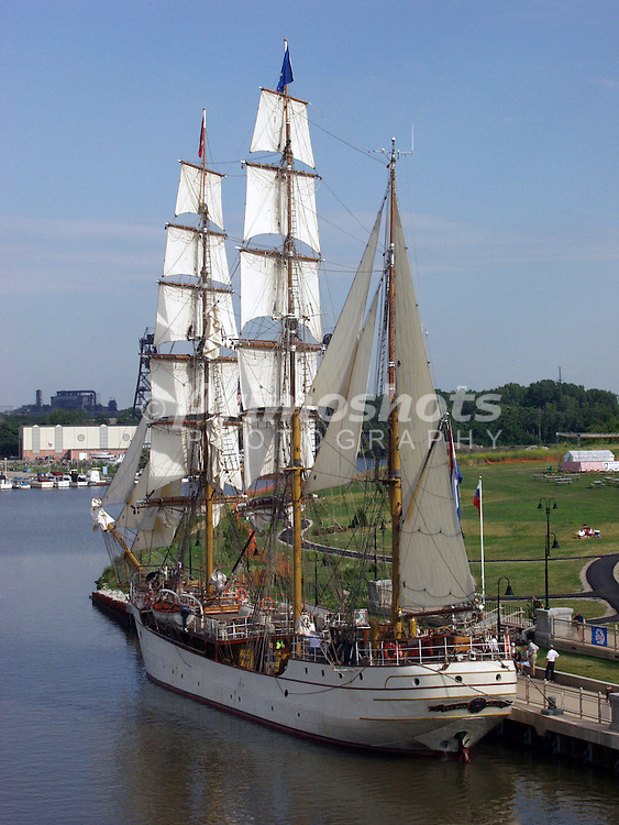 A tall ship is docked on the river.