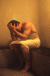 man wearing only a towel, sitting in a titled steam room