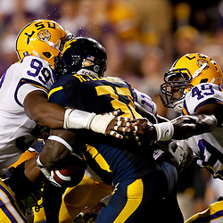 Sep 25, 2010; Baton Rouge, LA, USA; LSU Tigers defensive end Sam Montgomery (99) and defensive end Barkevious Mingo (49) combine to tackle West Virginia Mountaineers running back Ryan Clarke (32) during the first half at Tiger Stadium.  Mandatory Credit: Derick E. Hingle