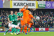 Netherlands defender Virgil van Dijk (4) looks to clear the ball as Northern Ireland midfielder Corry Evans (13) tries to get to the ball during the UEFA European 2020 Qualifier match between Northern Ireland and Netherlands at National Football Stadium, Windsor Park, Northern Ireland on 16 November 2019.