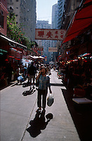 A woman talks on her cellphone while shopping at a market, Hong Kong, China.