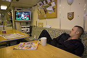 Royal Navy crewman watches TV in the Junior Ratings wardroom aboard HMS Vigilant, a Vanguard class nuclear submarine