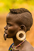 Mursi tribe woman with lower lip and earlobe modifications to hold clay discs , Mago National Park, Omo Valley, Ethiopia.