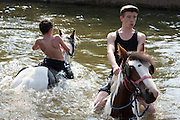 Gypsy boys ride their horses into the river Eden at the Appleby Horse Fair in Cumbria, England, United Kingdom. The horses are taken into the river and washed in preparation to be sold. Around 40,000 gypsy travellers congregate annually for the fair, one of the oldest and largest in Europe.