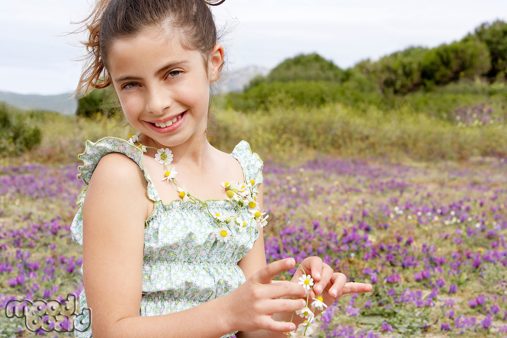 Smiling Pre-teen wearing and holding necklace of flowers in field of flowers