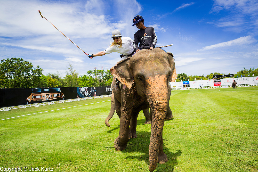 """28 AUGUST 2013 - HUA HIN, PRACHUAP KHIRI KHAN, THAILAND: KRISTIN GRUBE takes a swing at a polo ball during the King's Cup Elephant Polo Tournament in Hua Hin, Thailand. The tournament's primary sponsor in Anantara Resorts and the tournament is hosted by Anantara Hua Hin. This is the 12th year for the King's Cup Elephant Polo Tournament. The sport of elephant polo started in Nepal in 1982. Proceeds from the King's Cup tournament goes to help rehabilitate elephants rescued from abuse. Each team has three players and three elephants. Matches take place on a pitch (field) 80 meters by 48 meters using standard polo balls. The game is divided into two 7 minute """"chukkas"""" or halves. There are 16 teams in this year's tournament, including one team of transgendered """"ladyboys.""""     PHOTO BY JACK KURTZ"""