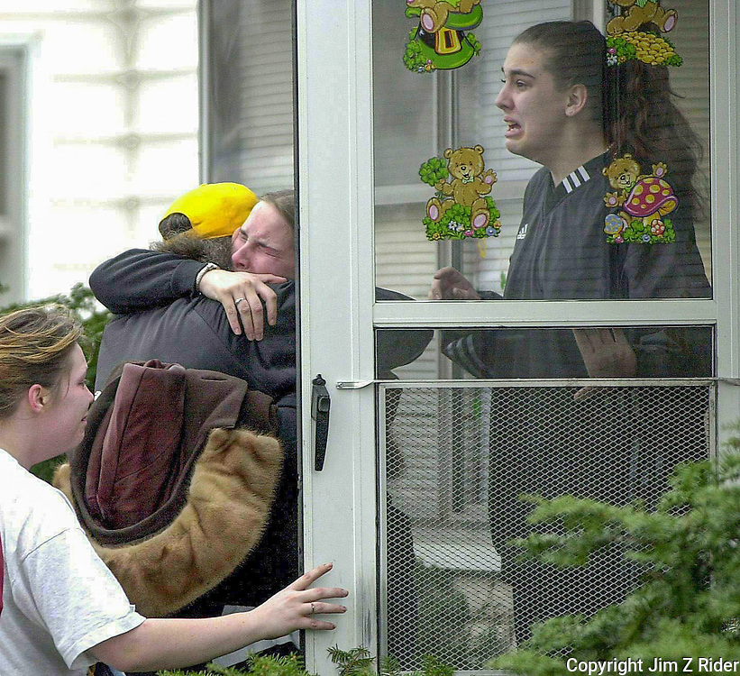 Family members mourn as firefighters remove the bodies of two young children killed in a house fire.  The babysitter was asleep on the couch and wearing headphones when a wood burning stove malfunctioned.