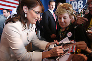U.S. Republican vice presidential nominee Governor Sarah Palin autographs a magazine for a supporter after a campaign rally in Cedar Rapids, Iowa, September 18, 2008.