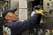 26 February 2013. Bronx, New York. Engine Co. 73/Hook & Ladder 42 at 655-659 and 661 Prospect Ave., the Bronx. Fireman Bill Schauffer stuffs his uniform into a cubby in the fire engine at Engine Co. 73, after returning from an emergency call. Schauffer was also stealing a quick smoke within the firehouse, which he confided was against the rules. 2/26/13. Photograph by Nathan Place/CUNY Journalism Photo