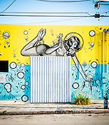 A giant pin-up wears a bubble-like diving helmet and a two-piece bathing suit in a whimsical, 1950s-ish, science fiction-like mural in Miami's Wynwood arts district painted by an Amsterdam-based  collective known as The London Police.