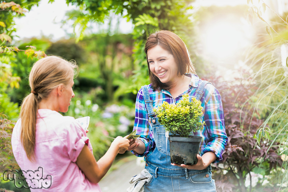 Portrait of woman buying plant on a pot from gardener