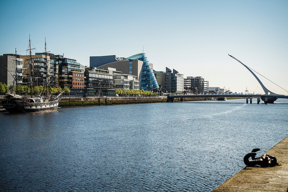 May 2012, Dublin City, Ireland: Looking up along the river Liffey towards the port of Dublin we see the new Samuel Beckett bridge and the national conference centre on a bright blue may morning. In the forground is the famous tall ship, the Jeanie Johnston.