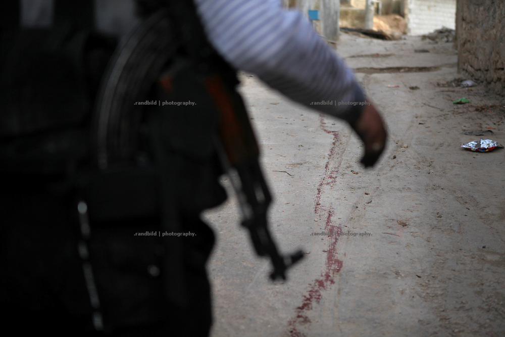 An Soldier of the Free Syrian Army follows a blood trail on a street in Kureen. An injured man was pulled to death fixed at an army during the assault on Kureen. On 22. February the syrian army attacked the village of Kureen, Province of Idlib, Syria. Kureen was among the first villages in the northwest of Syria controlled by the opposition. Some villagers and members of the defence units escaped to surrounding olive orchards, when the attack begun in the early morning. A majority of the inhabitants didn´t manage to escape. The heavy shelling lasts 7 houres. Soldiers searched all houses, burnt some of them down, loote shops, stole cars and furniture. About 60 motorcycles were burnt down. Tanks demolished several houses. 6 men were executed. One woman died as a result of an heart attack.