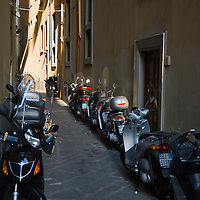Scooters parked in an narrow street, Florence, Italy