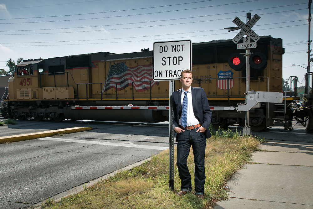 Chris Ihle, of Ames, Iowa, is pictured next to the site where he pushed a stalled car, with an elderly couple inside, off the tracks as a freight train bared down on the car.