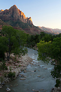 The Watchman stands guard over the Virgin River as the last rays of sun light its peaks. Zion National Park, UT