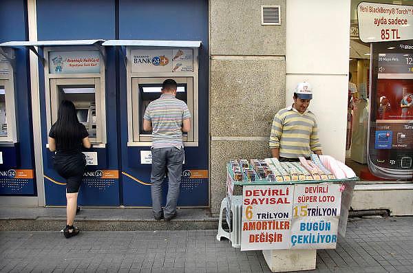 Turkije, Istanbul, 4-6-2011Straatbeeld van Istanbul in de aanloop naar de verkiezingen voor het parlement op 12 juni. Man en vrouw halent geld uit een pinautomaat van de Halkbank. Een lotenverkoper van een loterij staat ernaast.Foto: Flip Franssen